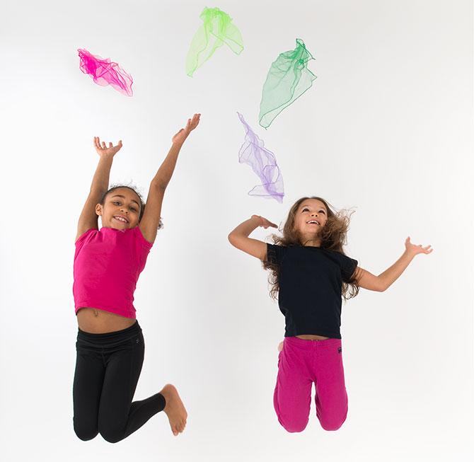 två barn hoppar och kastar sjalar